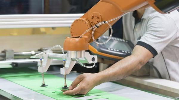Operario ajustando el brazo de un robot colaborativo